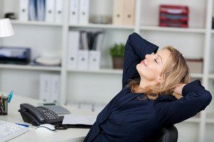 Businesswoman Relaxing With Hands Behind Head